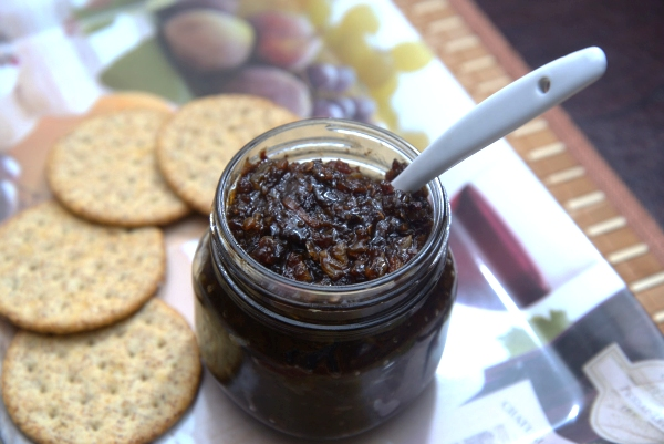 A small open jar containing Bacon, Chili, Raisin Relish on a tray with crackers