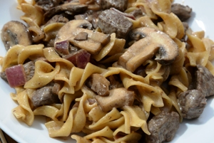 White plate containing beef stroganoff with German egg noodles