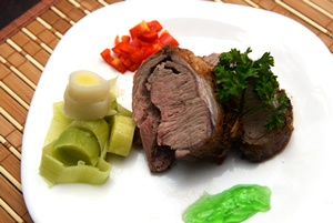 slices of a boneless lamb loin on a plate with steamed leeks, mint sauce and red bell pepper