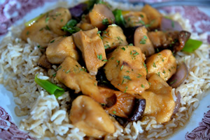Plate containing chicken with black mushrooms on a bed of brown basmati rice