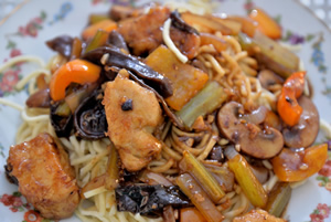 Plate containing Chicken & Wood Ear Mushrooms in Garlic Sauce on a bed of Chinese noodles