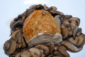 a white plate with half a roasted chicken breast and sautéed mushrooms