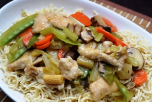A dish containing Chinese chicken and pineapple stir fry on a bed of Chinese noodles