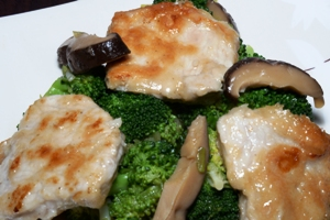 A dish containing Chinese pork, broccoli and black mushrooms