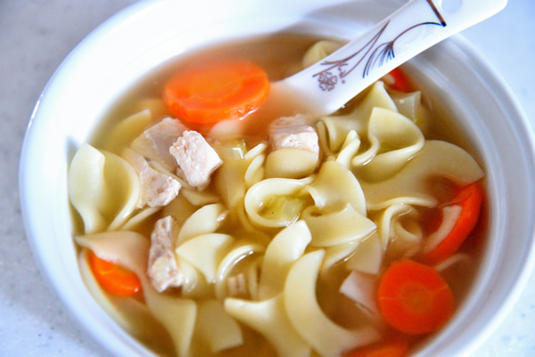 a white bowl containing Chicken Noodle Soup