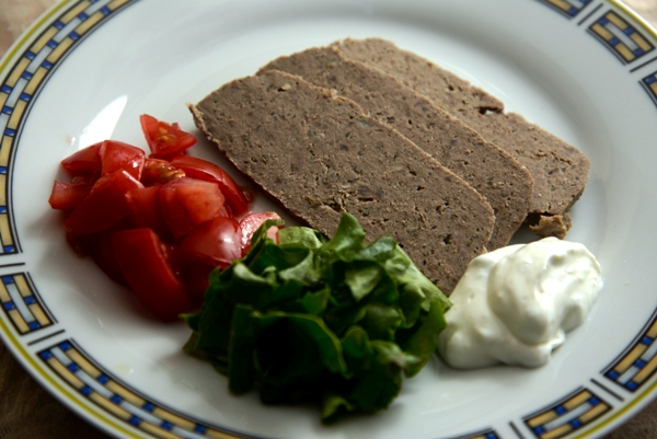 Gyro meat on a white plate with lettuce, tomatoes and tzatziki sauce