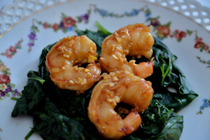A plate with a flower design has 3 honey garlic shrimp on a bed of spinach.