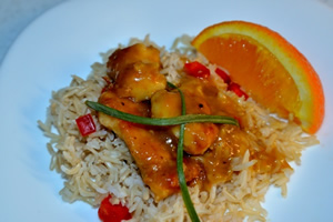A plate containing a Orange chicken served on a bed of brown Basmati rice