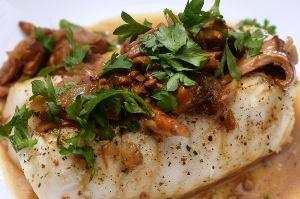 Chilean Sea Bass covered with Chantrelle Mushrooms and Italian parsley on a white plate
