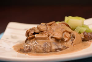 Steak Diane with braised leeks on a tan plate